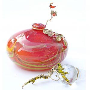 flacon rouge avec cordon jaune et bouchon avec dragon aux ailes en perles jaunes